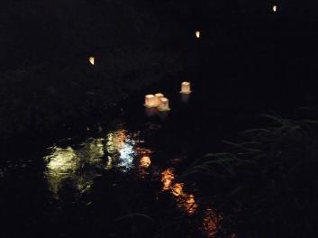 提灯の映る川面をゆく