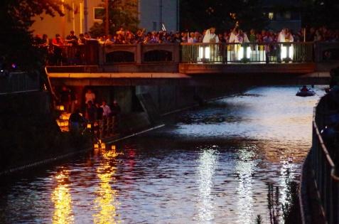 読経の中、灯籠が川に