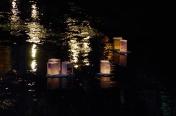 街明かり映る川面を行く灯籠